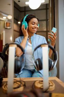 Frau, die musik im kopfhörerspeicher hört. weibliche person im audio-shop, schaufenster mit kopfhörern, käufer im multimedia-shop