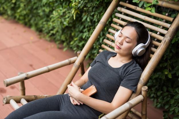 Frau, die musik im park nachdem dem laufen hört