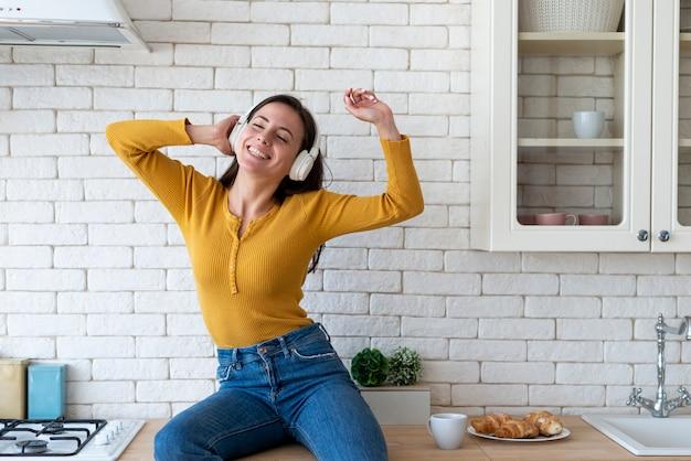 Frau, die musik in der küche genießt