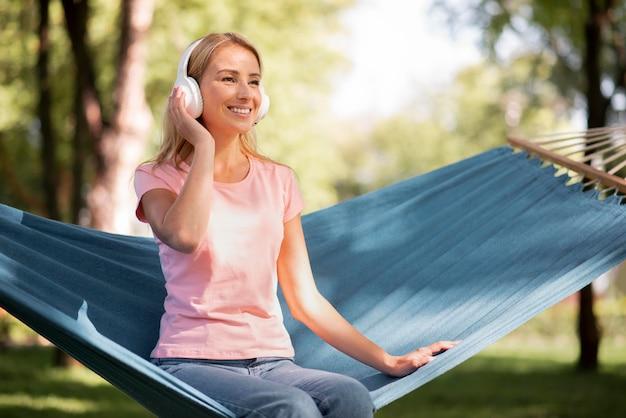 Frau, die musik in der langen ansicht der hängematte hört