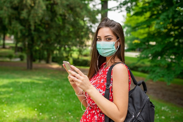 Frau, die musik in einem park während der coronavirus-pandemie hört