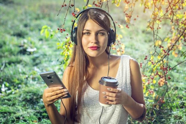 Frau, die musik in ihren tragenden kopfhörern des telefons an einem sonnigen tag hört.