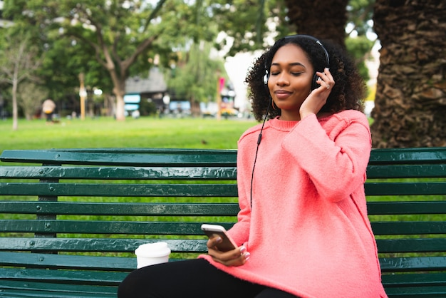 Frau, die musik mit ihrem telefon hört