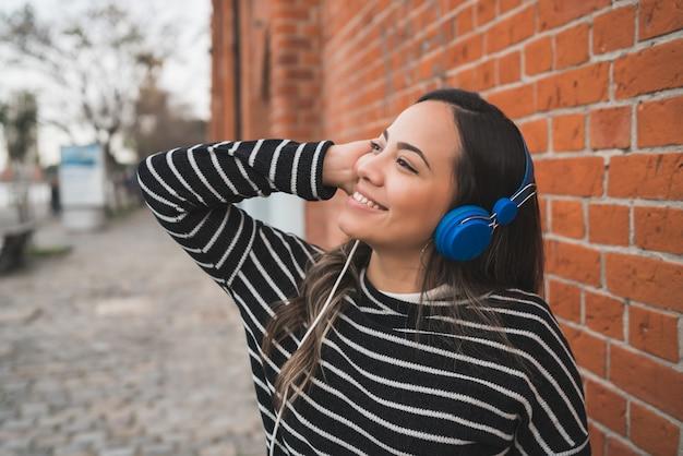 Frau, die musik mit kopfhörern hört