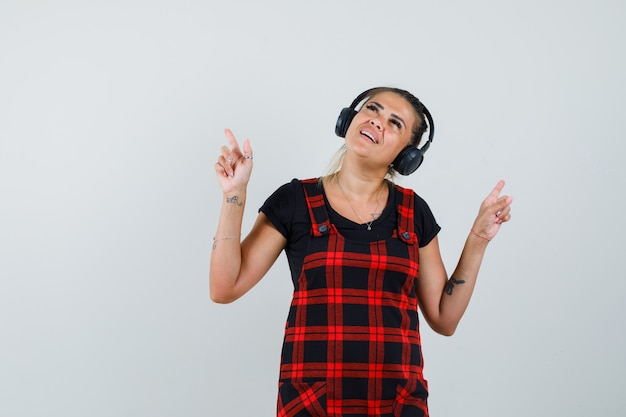 Frau, die musik mit kopfhörern im trägerkleid genießt und munter aussieht. vorderansicht.