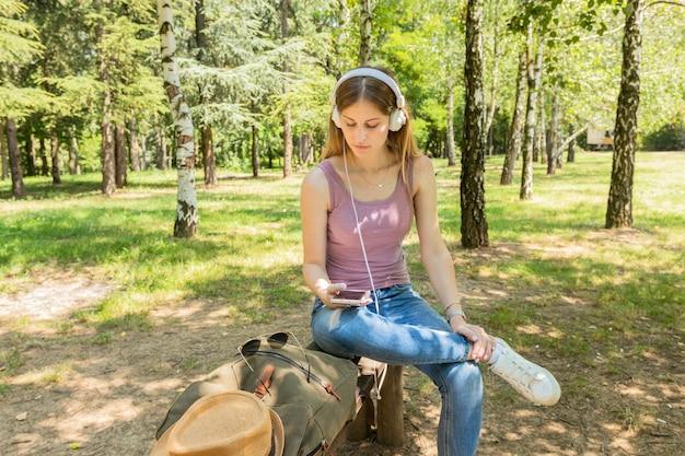 Frau, die musik mit kopfhörern sitzt und hört