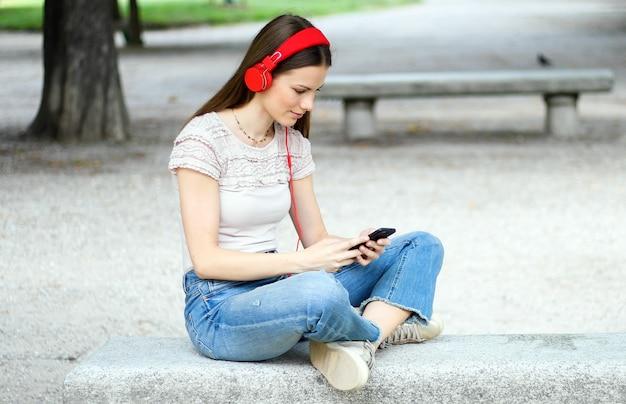 Frau, die musik sitzt auf bank in einem park hört
