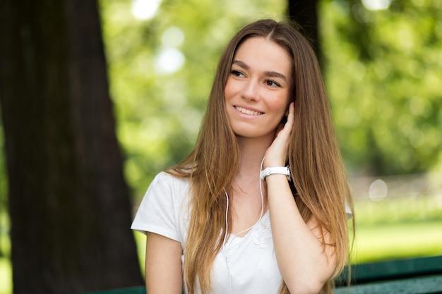 Frau, die musik sitzt auf einer bank in einem park an einem sonnigen tag des heißen sommers hört