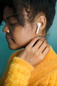 Frau, die musik über digitales gerät mit drahtlosen kopfhörern genießt
