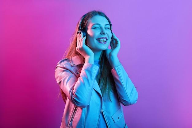 Frau, die musik über kopfhörer hört, die lieblingslieder genießt, hält die augen geschlossen und lacht glücklich