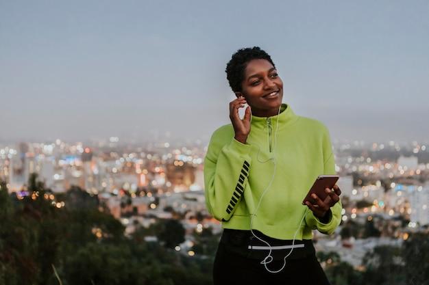 Frau, die musik von einem telefon hört