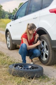 Frau, die muttern auf dem flachen rad des autos auf dem feld abschraubt
