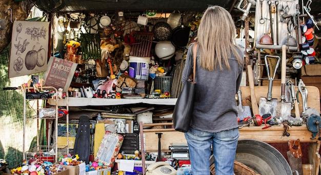 Frau, die nach etwas sucht, um in einem antiquitätenmarkt zu kaufen
