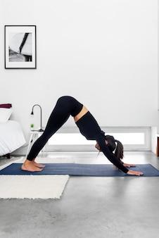Frau, die nach unten gerichteten hund mit online-yoga-trainingsprogramm im laptop zu hause tut