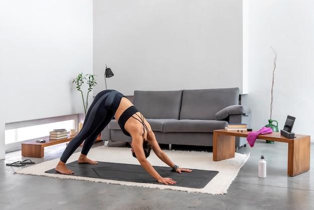 Frau, die nach unten gerichteten hund unter verwendung des online-yoga-trainingsprogramms in der tablette zu hause tut