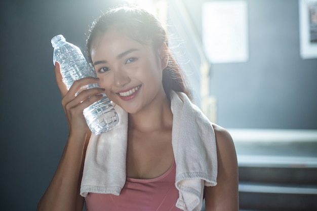Frau, die nachdem dem trainieren, eine flasche wasser anhalten steht und sich entspannt, um das gesicht zu berühren.