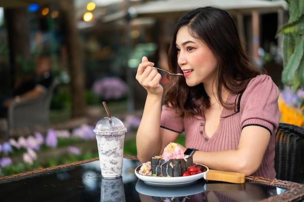Frau, die nachtisch im café isst