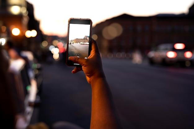 Frau, die nachts in den lichtern der stadt mit smartphone fotografiert