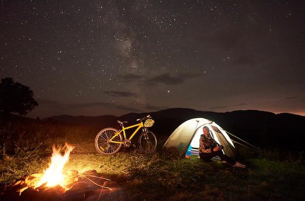 Frau, die nachts voll kampierend nahe lagerfeuer, touristisches zelt, fahrrad unter abendhimmel von sternen stillsteht