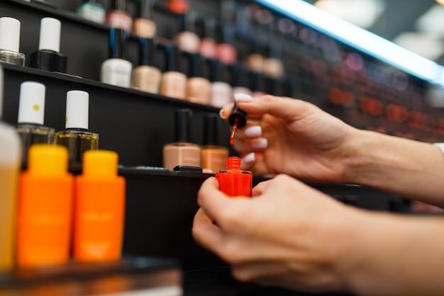 Frau, die nagellackfarbe im kosmetikgeschäft wählt. käufer im luxus-schönheitssalon, kundin im modemarkt