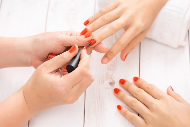 Frau, die nagelmaniküre erhält maniküre, die dem kunden roten nagellack aufträgt.