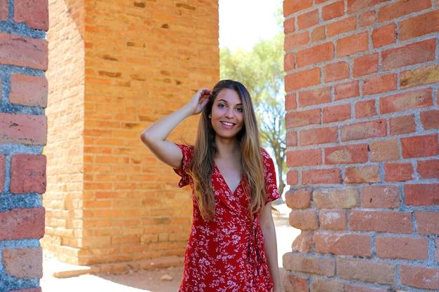 Frau, die nahe altem römischem torbogen im alten theater taormina, sizilien, italien aufwirft