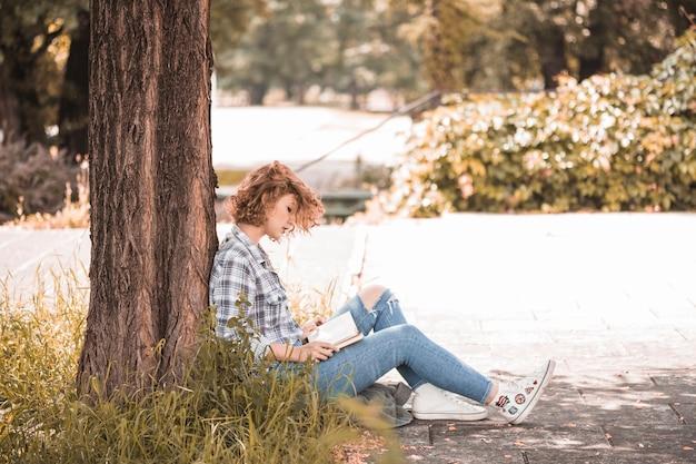 Frau, die nahe baum und lesebuch sitzt
