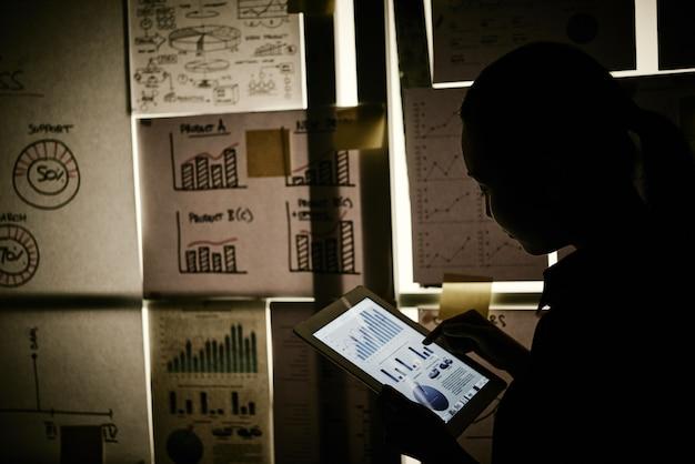 Frau, die nahe bei dem fenster bedeckt mit geschäftsdiagrammen steht und an tablette arbeitet