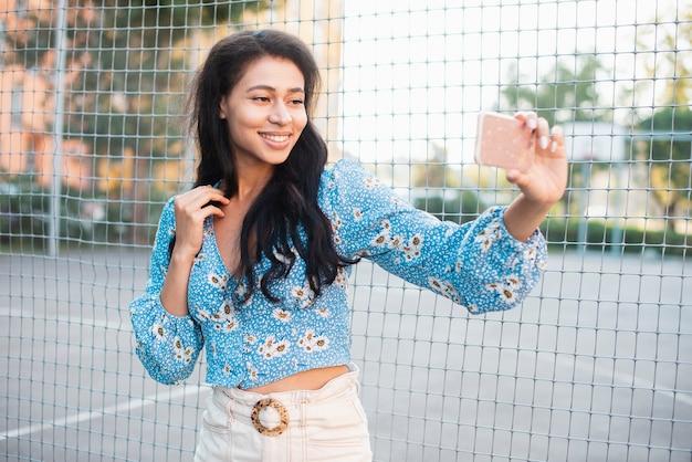 Frau, die nahe bei einem basketballplatz macht ein selbstfoto steht
