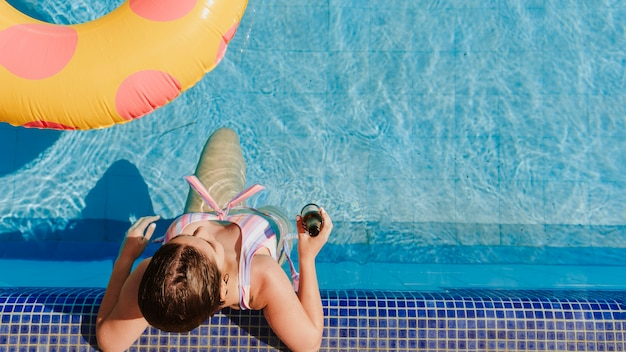 Frau, die nahe bei swimmingpool sich entspannt