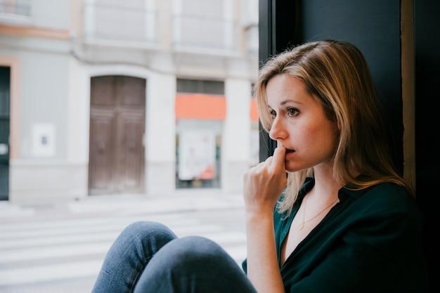 Frau, die nahe caféfenster denkt