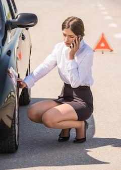 Frau, die nahe defektem auto sitzt und um hilfe am telefon ruft.