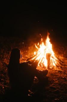 Frau, die nahe dem feuer im nachtwald sitzt und warm wird