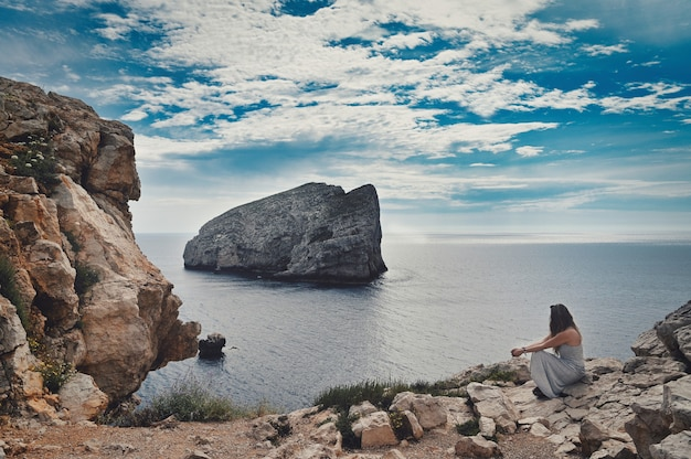 Frau, die nahe dem meer sitzt