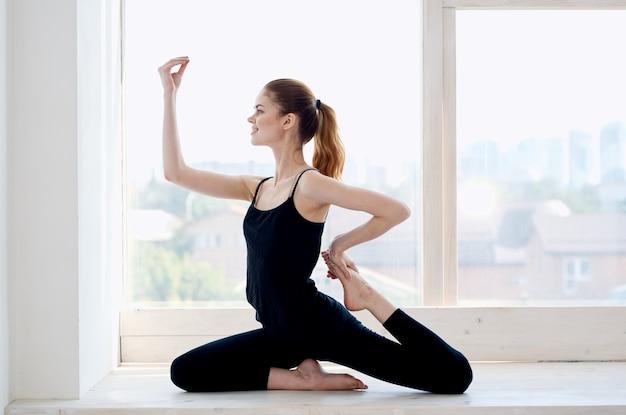 Frau, die nahe der fensteryoga-asana-meditation trainiert