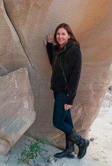 Frau, die nahe einer aufwerfenden klippe, amangiri, canyon point, unglücksbaum-spur, utah, usa steht