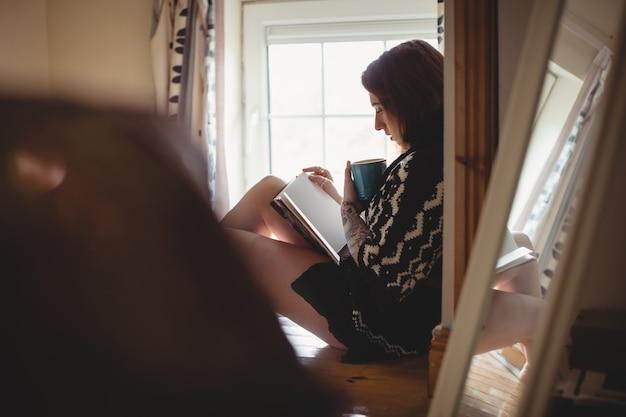 Frau, die nahe fenster sitzt und ein buch liest