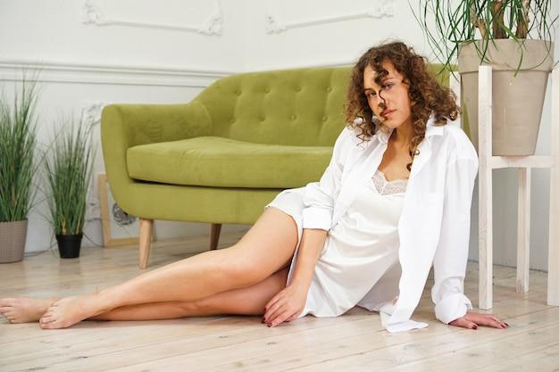 Frau, die nahe grünes sofa im wohnzimmer sitzt. schöne lange beine. schöne frau mit lockigem haar in weißen dessous zu hause - glücklicher morgen