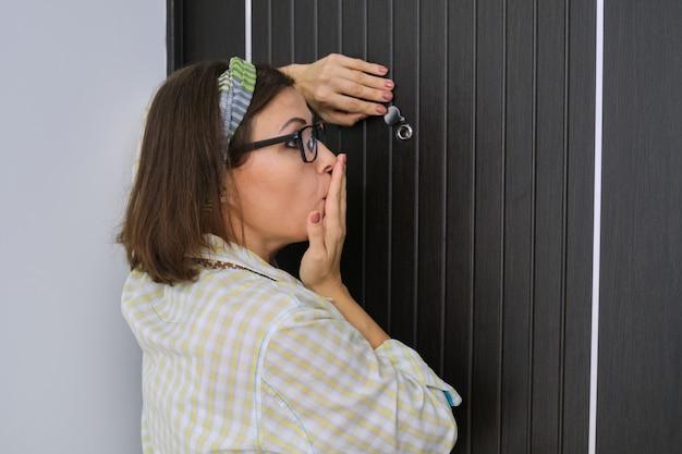 Frau, die nahe haustür steht und durch das guckloch schaut