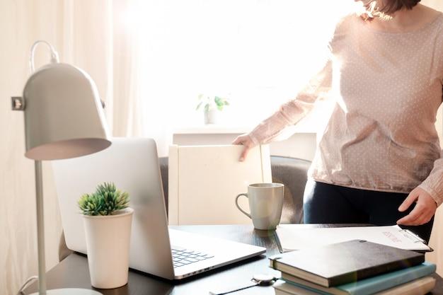 Frau, die nahe ihrem arbeitsplatz mit laptop und lebenslaufanwendung steht