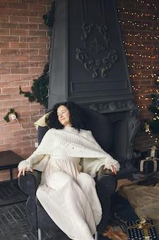 Frau, die nahe kamin sitzt. dame in einem weißen pullover. brünette in einem weihnachtskonzept.