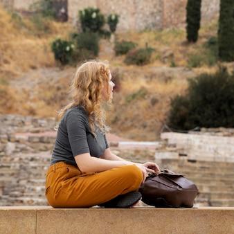 Frau, die nahe rucksack sitzt