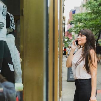 Frau, die nahe schaufenster telefoniert