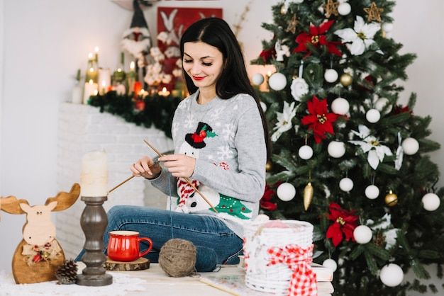 Frau, die nahe weihnachtsbaum strickt