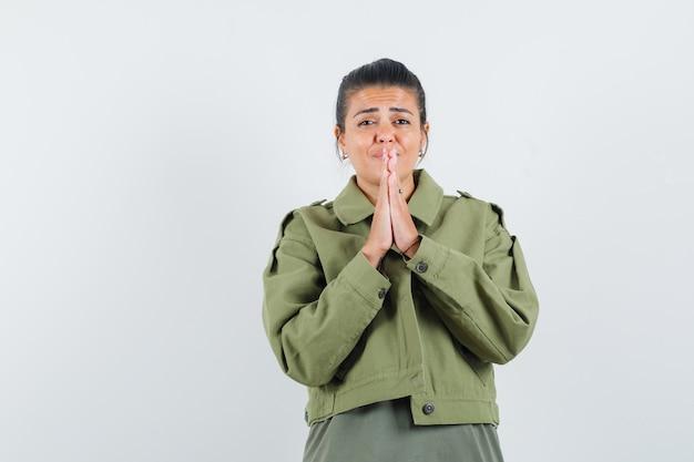 Frau, die namaste geste in jacke, t-shirt zeigt und verträumt aussieht