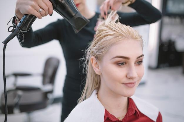 Frau, die nasses haar von blondine trocknet