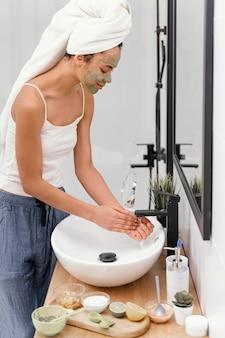 Frau, die natürliche bestandteile von ihren händen abwäscht