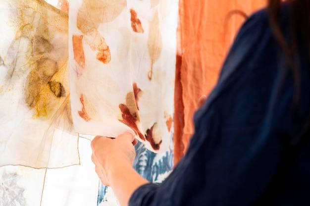 Frau, die natürliche pigmentierte tücher prüft