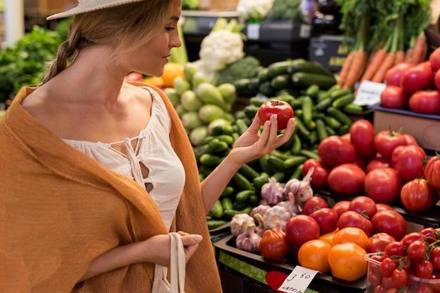 Frau, die natürliche produkte vom marktplatz kauft