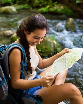 Frau, die natur erforscht und karte verwendet